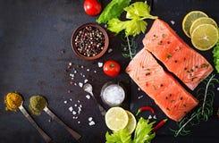 Ruwe zalmfilet en ingrediënten voor het koken op een donkere achtergrond in een rustieke stijl Royalty-vrije Stock Foto's