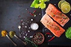 Ruwe zalmfilet en ingrediënten voor het koken op een donkere achtergrond in een rustieke stijl stock foto