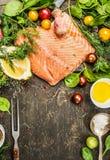 Ruwe zalmfilet met heerlijke verse aromatische kruiden, kruiden, groenten, citroen en olie op rustieke houten achtergrond, hoogst Royalty-vrije Stock Afbeeldingen