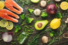 Ruwe zalmfilets en ingrediënten, groenten voor het koken op een donkere achtergrond in een rustieke stijl De hoogste mening, vlak royalty-vrije stock foto