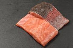Ruwe zalmfilets op een donkere leiachtergrond Filet van forel zonder kruiden Wilde Atlantische vissen stock afbeeldingen