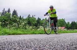 Senior woman cycling on bike trail royalty free stock photography
