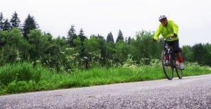 Senior man cycling on bike trail stock image