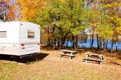 RV在湖岸露营地的秋天森林里野营 图库摄影