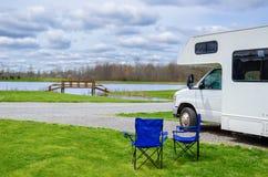 RV露营车和椅子在野营,家庭度假旅行,假日旅行由motorhome 免版税图库摄影