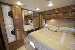 RV Bedroom. Recreation Vehicle Bedroom Interior with Washer and Dryer in Closet. Luxury Motorhome Bedroom Stock Photos