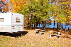 RV camped in fall forest on lakeshore campsite Stock Photography