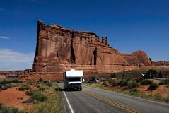 RV Camper driving in Arches National Park Utah USA. White RV touring camper van driving on tarmac road through Arches National Park. Courthouse Towers geological Stock Photo