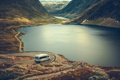 RV Camper Scenic Road Trip. Raw Norwegian Landscape and the Camper Van Recreational Vehicle on the Winding Mountain Road near Famous Village of Geiranger royalty free stock photography