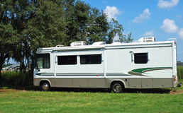 RV camper in the shade. RV parked in the shade of a tree stock photography