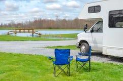 Rv-Camper und -stühle beim Kampieren, Familienurlaubreise, Feiertagsreise motorhome Lizenzfreies Stockfoto