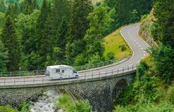 RV Camper Van Trip. Camper Van on the Mountain Road Bridge in Swiss Alps. Camper Traveling Stock Photography