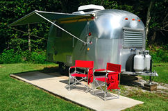 RV Camping. Classic american icon camper with two red chairs Stock Photo