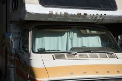 An RV with curtain covering the windshield is housing for Bay Area Residents, CA. An RV or recreational vehicle or trailer is parked on a city street in Stock Image