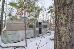 Rv dilapidado abandonado com a porta aberta nas madeiras em Wisconsin do norte rural no inverno imagens de stock