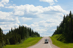 RV drives Alcan south Fort Nelson BC Canada. Recreational Vehicle RV on empty road of Alaska Highway, Alcan, in boreal forest taiga landscape south of Fort royalty free stock image