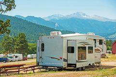 RV Fifth Wheel Camping. Travel Trailer with Extended Sliders in the Mountain Campground royalty free stock photography