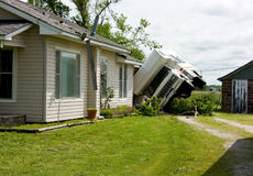 RV On Its Side Storm Damage. An RV or recreational vehicle turned on its side against a house after a tornado passed through the area Royalty Free Stock Images