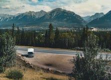 Rv met lege straat met bergpanorama in de Nationale Pa van Banff stock foto's