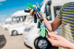 RV Motorhome Salesperson. RV Camper Vans and Motorhomes Salesperson with Keys To Vehicles on the Dealer Lot royalty free stock image