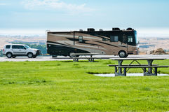 RV  Recreational Vehicle. Luxury recreational vehicle with car in tow parked in rest area park. Picnic tables in foreground. Washington State, USA. Horizontal Stock Photo