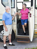 RV Seniors - Chivalry. Polite senior man helps his wife down the stairs of their motor home Stock Image