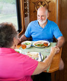 RV Seniors - Dinner Conversation. Senior couple enjoys conversation over a healthy meal in their motor home Royalty Free Stock Photography