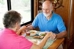 RV Seniors - Mealtime Prayer. Christian senior couple in their motor home, saying grace over their meal Royalty Free Stock Photography