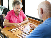 RV Seniors Play Backgammon. Senior couple enjoys a game of backgammon in their motor home Stock Photos