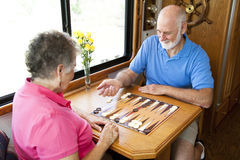 RV Seniors Playing Board Game. Senior couple on vacation playing backgammon in their motor home.  Motion blur on the man's hand as he shakes the dice Royalty Free Stock Photo