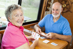 RV Seniors - Playing Cards. Happy retired couple playing cards in their motor home Stock Image