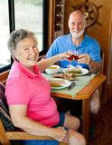 RV Seniors - Romantic Meal. Senior couple enjoys a romantic meal in the kitchen of their motor home Royalty Free Stock Photography