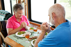 RV Seniors - Saying Grace. Christian senior couple saying grace over a meal in their motor home Royalty Free Stock Photo