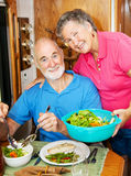 RV Seniors - Serving Dinner. Senior woman serves a healthy dinner to her husband in their modern motor home Royalty Free Stock Photo