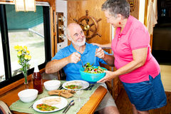 RV Seniors - Serving Salad. Senior couple enjoying a healthy meal in their luxury motor home Stock Photos