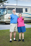 RV Seniors Thumbs Up. Senior couple in front of their luxury RV, giving thumbs up sign Royalty Free Stock Images