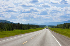 RV southbound Alcan Fort Nelson BC Canada. Recreational Vehicle RV southbound on empty road of Alaska Highway, Alcan, in boreal forest taiga landscape south of royalty free stock photography