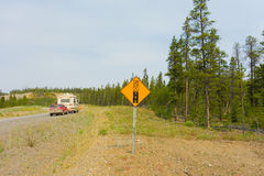 An rv and tow car approaching a gravel road in the yukon territories. A lonely stretch of the alaska highway in the springtime Royalty Free Stock Photos