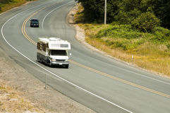 RV travel. A motorhome travels along a highway en route to a campground Royalty Free Stock Photo