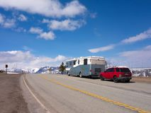 A motor home towing a car to a mountain summit in the springtime Stock Photography