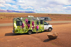 RV Vacation Travel America West. A young girl standing in front of an RV covered in Colorado wildflowers. Location is on highway 89 just past Marble Canyon Royalty Free Stock Photo