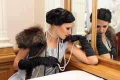 Rêver la belle femme s'asseyant au miroir Photo stock