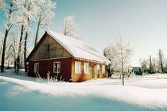 Árvores no hoarfrost, casa vermelha na manhã Imagens de Stock