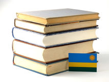Rwanda flag with pile of books isolated on white background. Rwanda flag with pile of books isolated on white Stock Photo