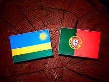 Rwanda flag with Portuguese flag on a tree stump isolated. Rwanda flag with Portuguese flag on a tree stump vector illustration