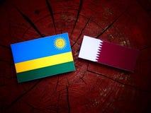 Rwanda flag with Qatari flag on a tree stump isolated Royalty Free Stock Image