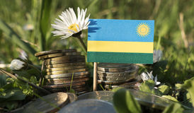 Rwanda flag with stack of money coins with grass Stock Photo
