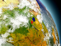 Rwanda from space. Rwanda in red on model of planet Earth with embossed countries and visible country borders. 3D illustration with clouds and reflective ocean Stock Photo