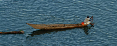 Rwandan Man Paddles Long Boat pulling Logs. A lone African man paddles his long boat across a lake while pulling some logs stock image