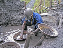 Rwandan Miner Panning For Precious Metals. The miner is hand-panning precious metals - tungsten and tantalum - that are widely used in the electronics industries Royalty Free Stock Photography